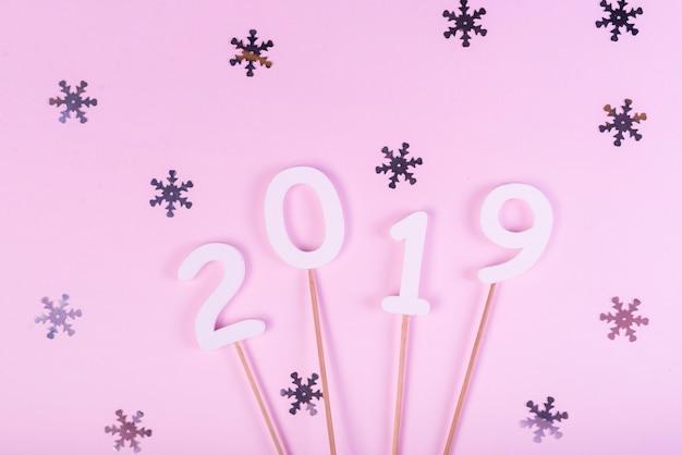 Chiffres 2019 sur des bâtons avec des flocons de neige scintillants