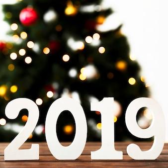 Chiffres blancs de 2019 sur la table devant le sapin