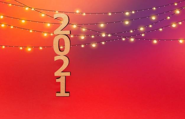 Chiffres en bois dans une casquette du nouvel an sur fond rouge avec une guirlande lumineuse.