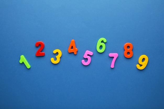 Chiffres multicolores magnétiques sur fond bleu avec espace de copie. retour à l'école.