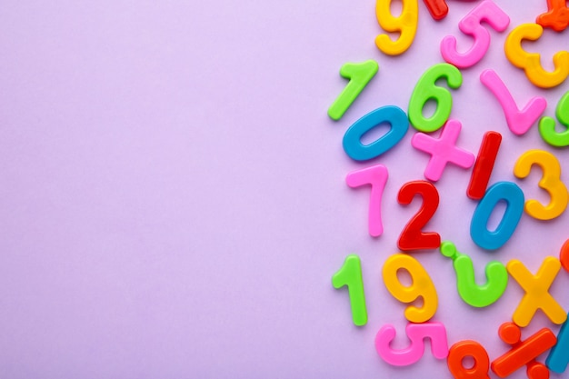 Chiffres multicolores magnétiques sur fond violet avec espace de copie. retour à l'école.
