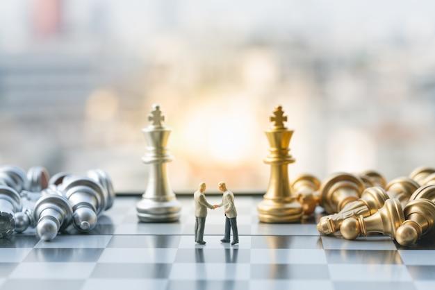 Chiffres de petit homme d'affaires vérifiant la main sur l'échiquier avec des pièces d'échecs.