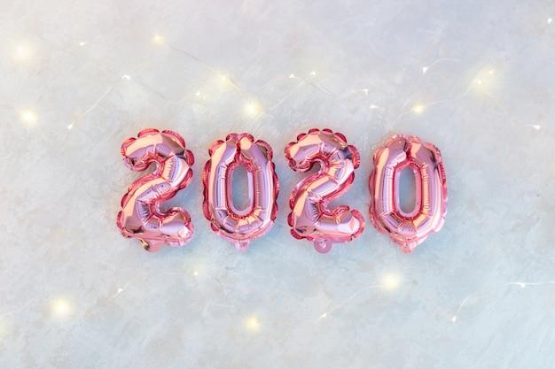 Chiffres roses 2020 sur du béton blanc, une guirlande d'étoiles scintillantes de lumières colorées.