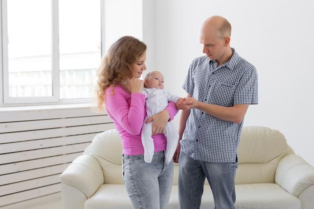 Childgood, parentalité, concept de personnes bébé sur les mains des parents sur un mur blanc.