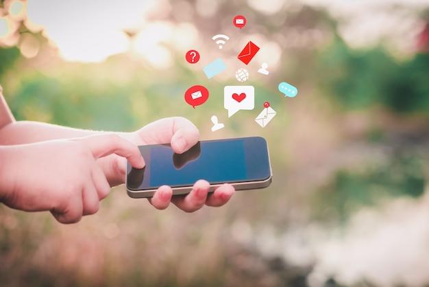 Childs hand using smartphone avec icône coeur et message d'enveloppe sur fond de nature