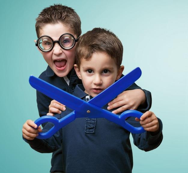 Childs avec des lunettes et des ciseaux bleu