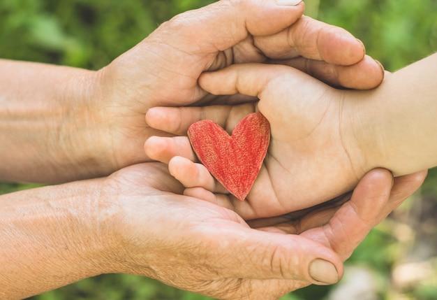 Childs main et vieille main grand-mère tenir coeur