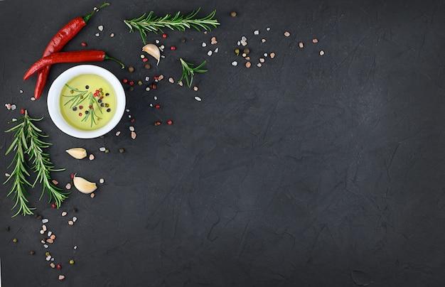 Chili, ail, huile et épices sur fond noir