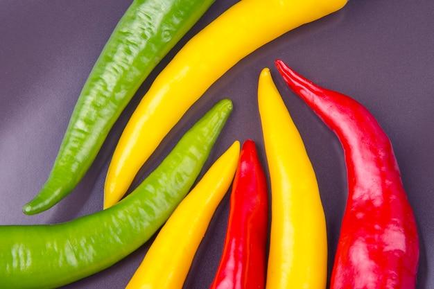 Chili chaud jaune, rouge et vert sur une assiette. poivre. nourriture vitaminée végétale.