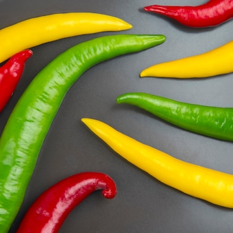 Chili chaud jaune, rouge et vert sur fond gris. poivre. nourriture vitaminée végétale.
