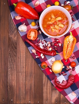 Chili con carne dans un bol en argile sur un fond rustique en béton ou en pierre- plat traditionnel de la cuisine mexicaine.vue de dessus.