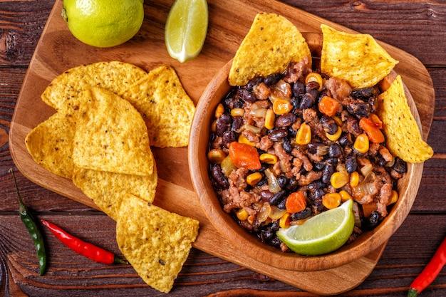 Chili con carne dans un bol avec des chips tortilla sur bois