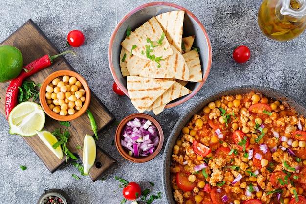 Chili con carne de dinde aux pois chiches servi avec des nachos. chili à la viande, nachos, citron vert, piment. cuisine traditionnelle mexicaine / texane. vue de dessus