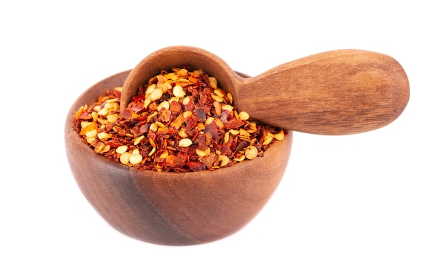 Chili et paprika dans un bol en bois et une cuillère, isolé sur blanc.