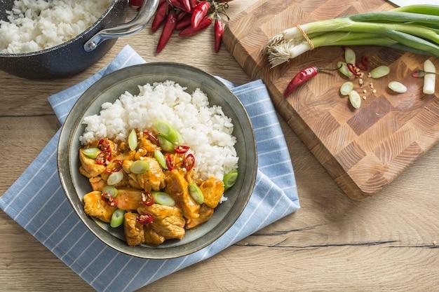 Chili de riz au curry de poulet et jeune oignon dans un bol.