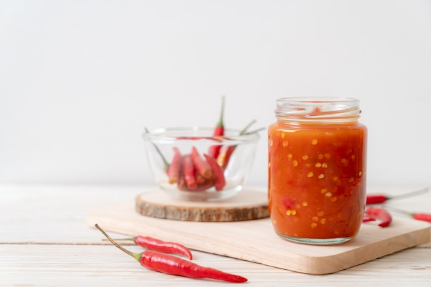 Chili ou sauce chili en bouteille et pot sur table en bois