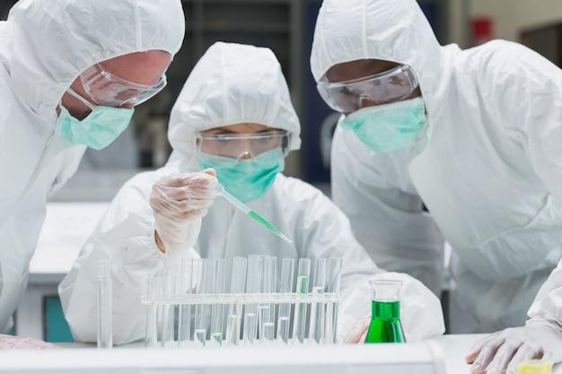 Chimiste ajoutant du liquide vert aux éprouvettes avec deux autres chimistes