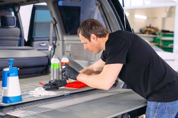 Chimiste automobile. traitement chimique du coffre de voiture.