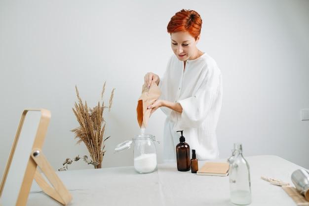 Un chimiste aux cheveux courts prépare un mélange pour des cosmétiques respectueux de l'environnement sur une table. verser la poudre blanche dans un bocal.