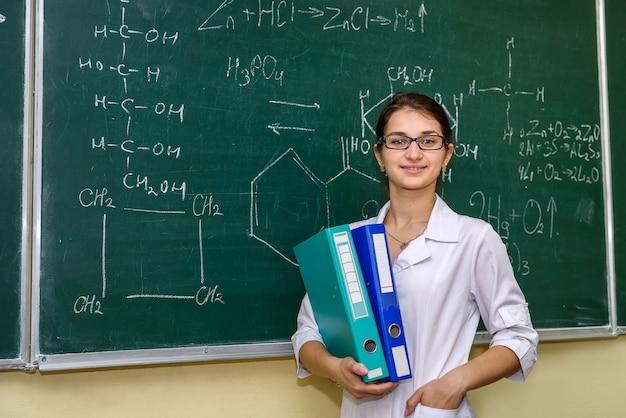 Chimiste avec dossiers debout et posant. derrière le conseil universitaire de femme avec des formules chimiques