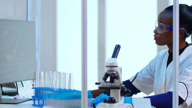 Chimiste de femme noire tapant sur pc vérifiant le développement du virus dans un laboratoire équipé moderne. médecin africain travaillant avec diverses bactéries, tissus, échantillons de sang, recherche pharmaceutique pour les antibiotiques