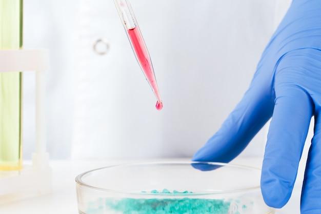 Chimiste mains tenant des éprouvettes avec des liquides et faisant des expériences
