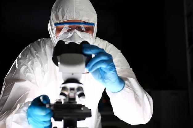 Chimiste scientifique analysant la recherche au microscope