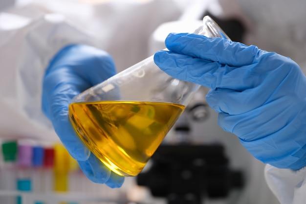 Chimiste scientifique dans des gants de protection en caoutchouc tenant une fiole avec un liquide jaune en gros plan