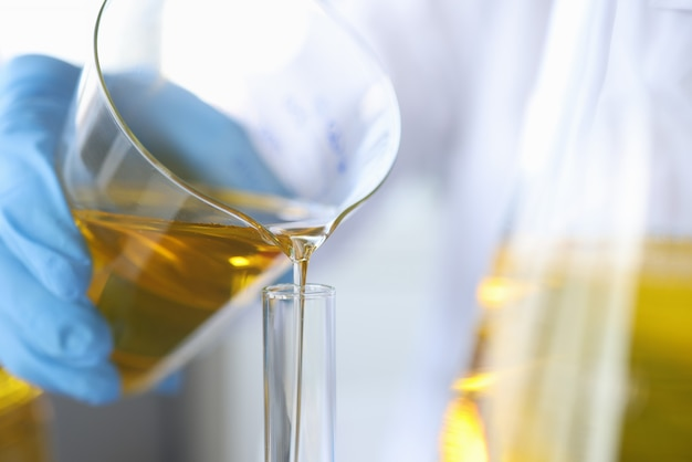 Chimiste scientifique verser de l'huile du flacon dans le contrôle de la qualité des huiles comestibles gros plan en verre