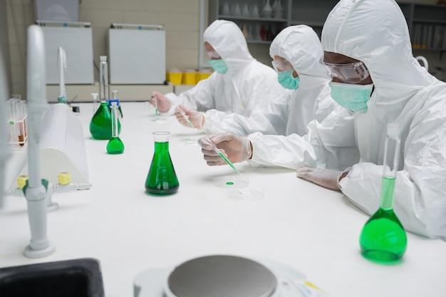 Chimistes testant le liquide vert dans des boîtes de pétri