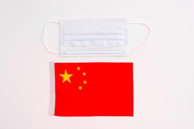 La chine tente de récupérer son économie en garantissant la sécurité sanitaire, concept de masque chirurgical sur drapeau chinois.
