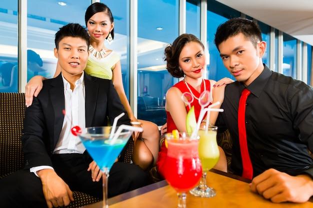 Des chinois boivent des cocktails dans un bar à cocktails de luxe