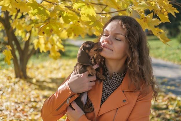 Chiot teckel mignon embrassant sa maîtresse dans le parc d'automne