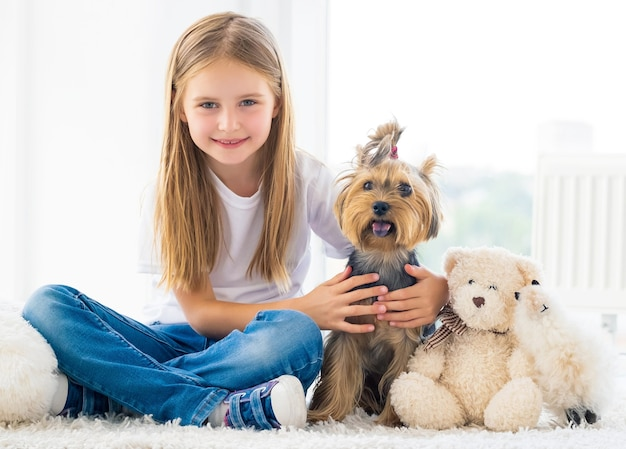 Chiot terrier et heureuse petite fille assise à l'intérieur