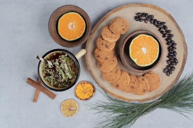 Chip cookies, grains et tranche de mandarine sur planche de bois.