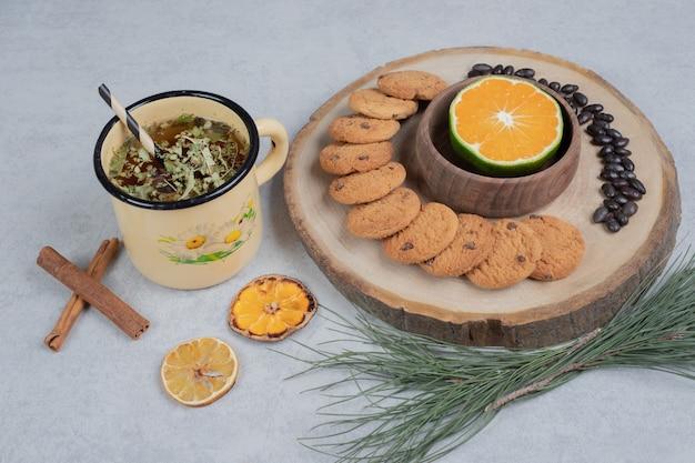Chip cookies et tranche de mandarine sur planche de bois avec tasse de thé. photo de haute qualité