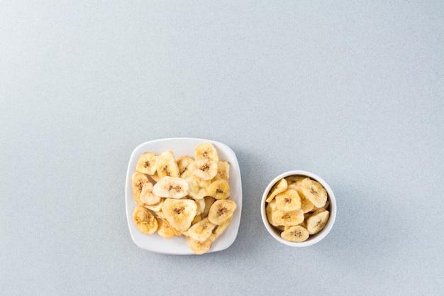 Chips de banane au four dans un bol blanc et soucoupe sur la table