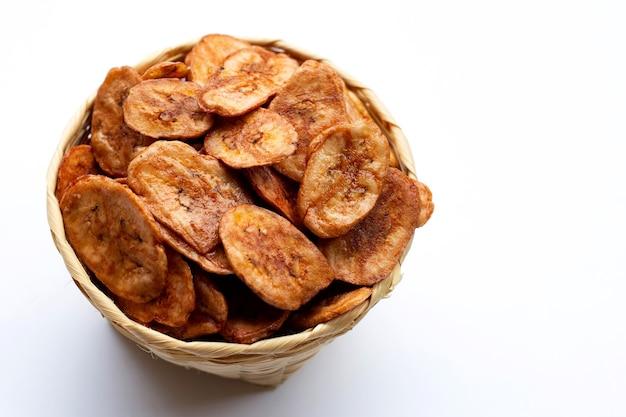 Chips de banane dans le panier sur une surface blanche