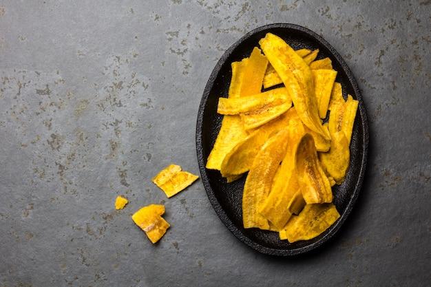 Chips de banane plantain sains faits maison sur plaque noire