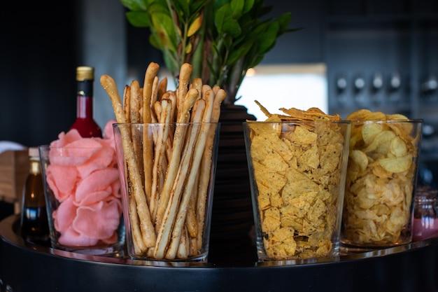 Chips et bâtons croustillants dans des tasses en verre
