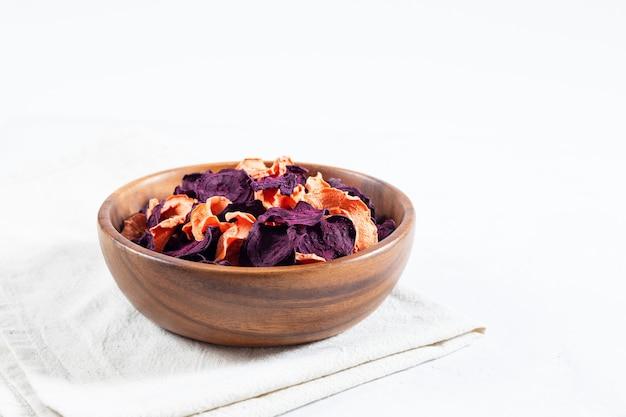Chips de carottes et betteraves séchées dans un bol en bois et carottes crues, betteraves sur fond de béton blanc.