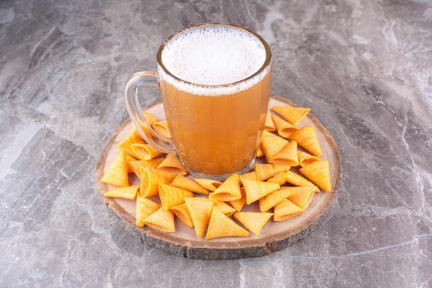 Chips croustillantes à la bière froide sur morceau de bois. photo de haute qualité