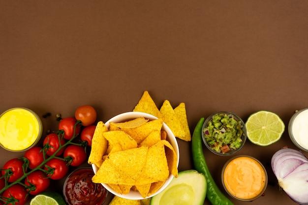 Chips croustillants de tortilla nachos dans un étui tareoque avec sauces et ingrédients. avec place pour le texte.