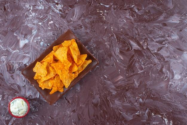Chips épicées sur une assiette à côté d'un bol de mayonnaise , sur la table en marbre.