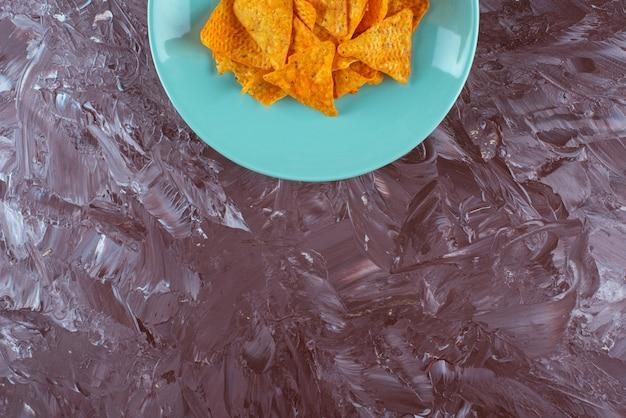 Chips épicées savoureuses sur une assiette , sur la table en marbre.