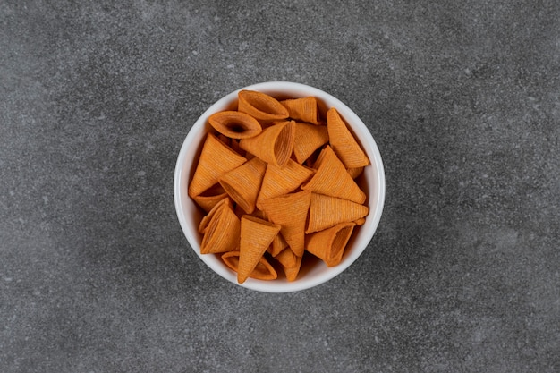 Chips en forme de triangle dans un bol blanc.