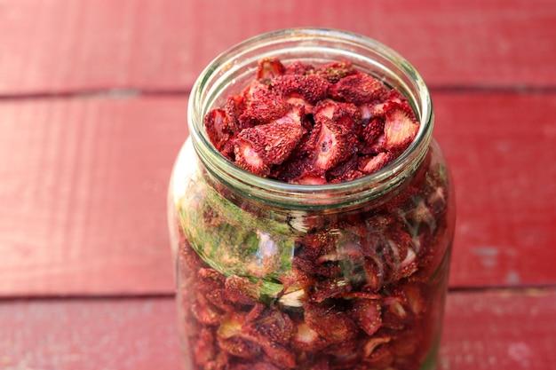 Les chips de fraises sont dans un bocal en verre, des aliments sains