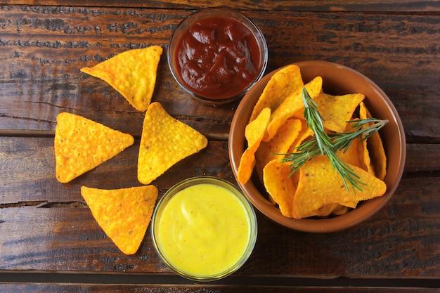 Chips de maïs nachos placés dans un bol en céramique sur une table en bois à côté de sauces assorties