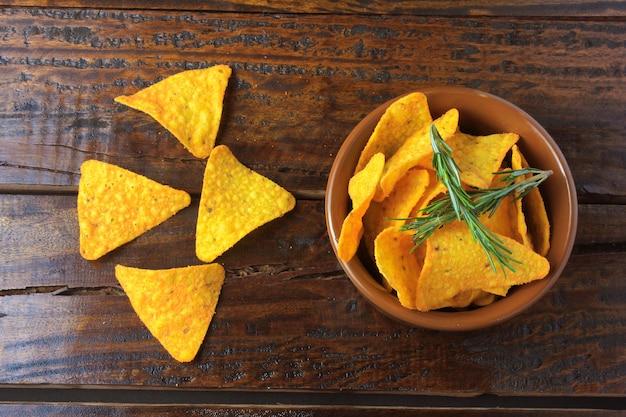 Chips de maïs nachos placés dans un bol en céramique sur une table en bois, espace de copie