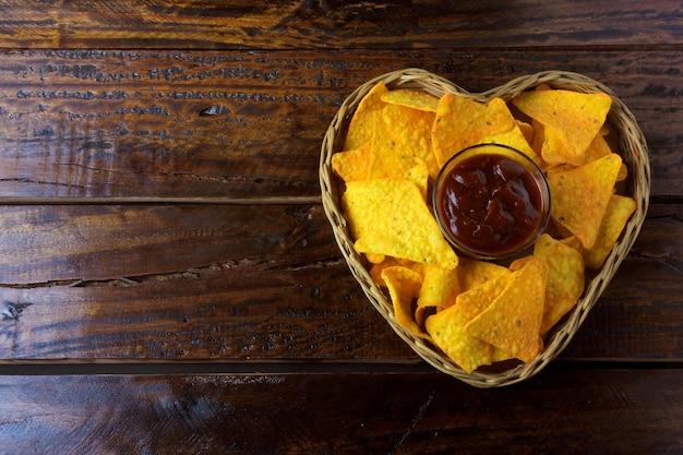 Chips de maïs nachos avec sauces placées dans un panier en forme de coeur sur une table en bois